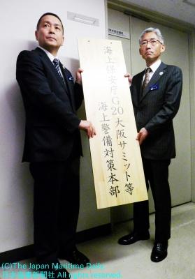対策本部の看板を立て掛ける岩並長官(右)と星警備救難部長