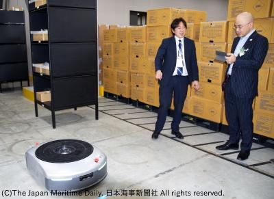 物流ロボット「イブ」の稼働現場を歩く西成氏(右)