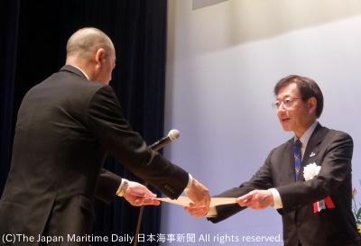 港湾勤労者に表彰状を手渡す久元市長(右)