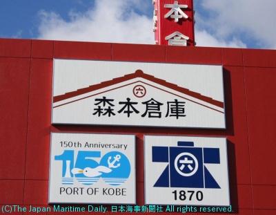 森本倉庫の生田川倉庫の壁面に掲示された新ロゴ(上)と神戸開港150年ロゴ(左下)