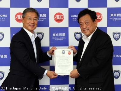 認定書を掲げる岡藤社長(左)と大森税関長