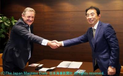 調印式で握手を交わす田中常務(右)とプラィアーCEO